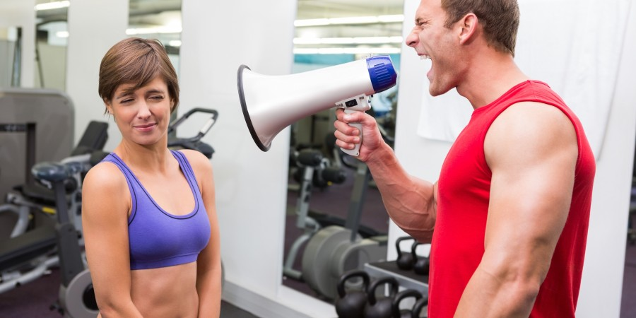 Personal trainer shouting at client through megaphone